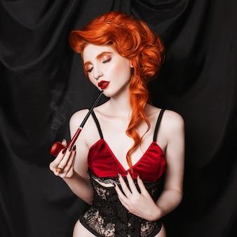 Рыжая женщина с вьющимися волосами выглядит в черном корсете и белье курит трубку на черном фоне. концептуальная фотография