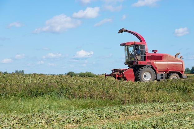 畑の赤い収穫機が穀物を集めています。