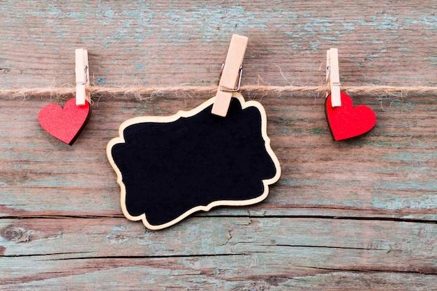 赤いハートと黒板の素朴な木製のテーブルに幸せなバレンタインデーのテキスト