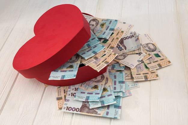 お金でいっぱいの赤いハート型の箱。ウクライナのuahマネー1000および500紙幣を机の上に