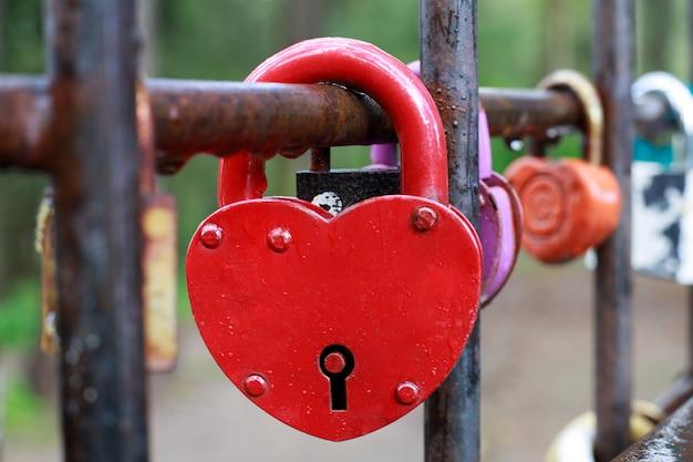 Красный замок в форме сердца, висящий на заборе.