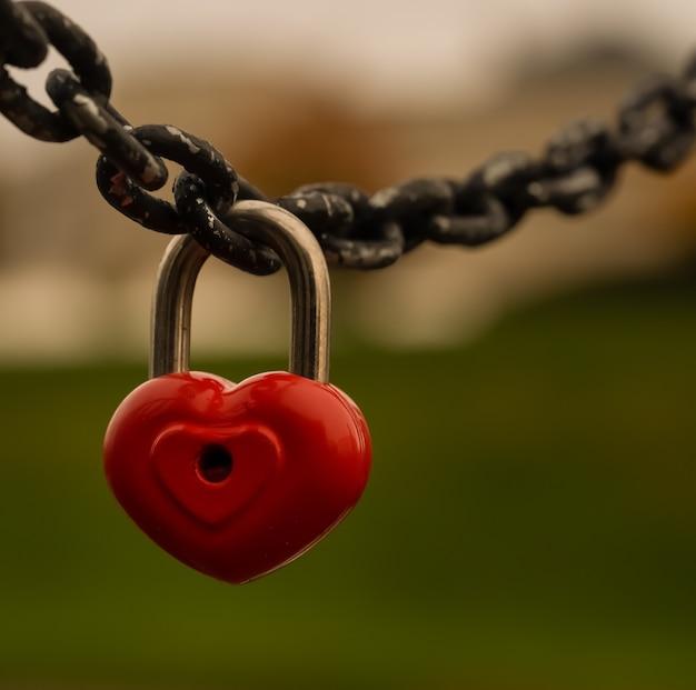 赤いハート型の南京錠がチェーンに掛かっています。これは愛と忠誠の象徴です。高品質の写真