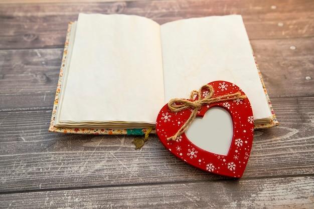 赤いハート型のフォトフレームが開いているノートブックにあります