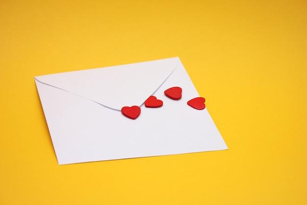 Красные сердца на белом почтовом конверте. Premium Фотографии