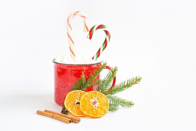 하트 모양의 마시멜로와 사탕 지팡이가 달린 빨간 머그는 천연 전나무 가지 또는 말린 오렌지 조각과 계피 스틱으로 장식되어 있습니다. 크리스마스와 새해, 휴가의 맛.