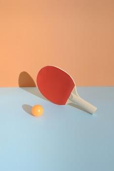 파란색 배경에 공이 앞에 있는 빨간색 탁구 라켓. 스포츠 탁구 정물 개념입니다.