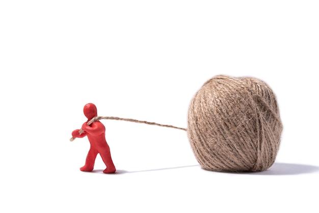 Красный пластилиновый человечек вытягивает из шара нитку