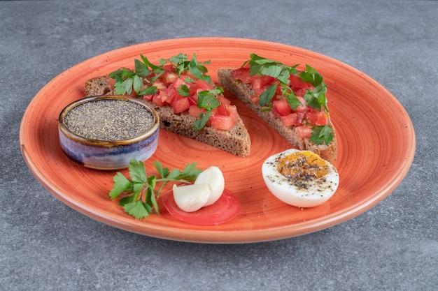 ゆで卵とトーストが入った赤いお皿。高品質の写真