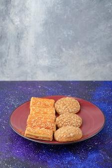 건강한 쿠키와 은하 테이블에 맛있는 크래커와 함께 빨간 접시.