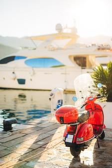 Красный ретро-мопед припаркован у пристани