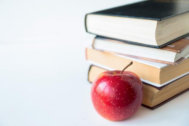 Красное спелое сочное яблоко возле книг