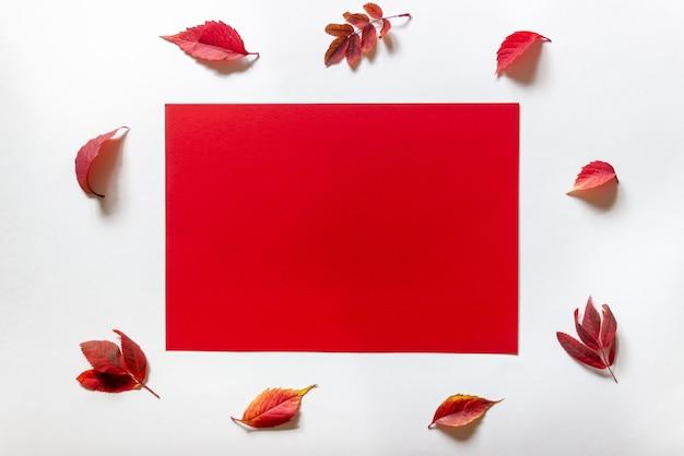 Красный лист бумаги на белом в окружении красных листьев.