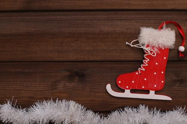 Красные ботинки для конька скользят по белой мишуре на коричневом деревянном фоне.