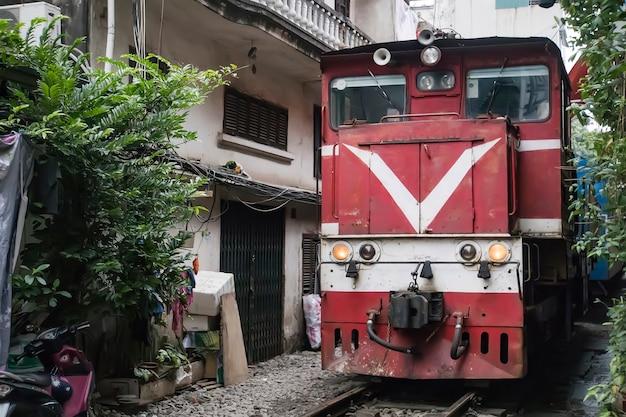 Красный локомотив едет по узкой улочке в бедном районе ханоя. узкий зазор между домами без мер предосторожности.