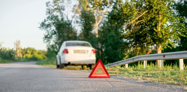 高速道路での自動車事故のシンボルとしての道路上の赤い三角形の標識
