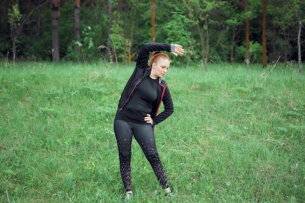 スポーツ服を着た赤毛の陽気な女性は、公園で太りすぎと健康的なライフスタイルを失うためにスポーツをします