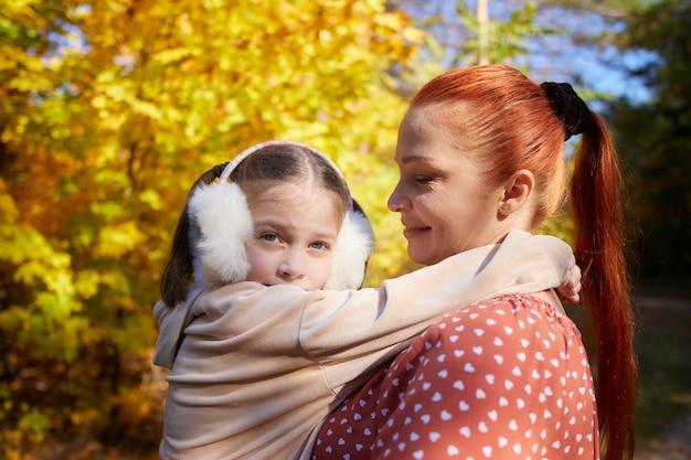 秋の日当たりの良い公園で彼女の腕に小さな娘を持つ赤毛の幸せな女性