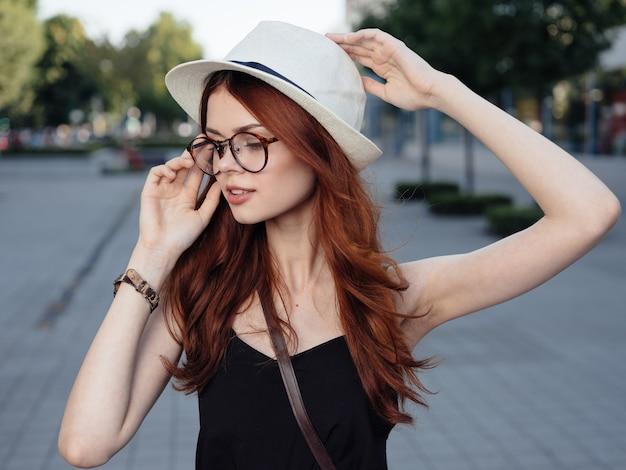 Рыжая женщина в белой шляпе и очках летом гуляет по улице