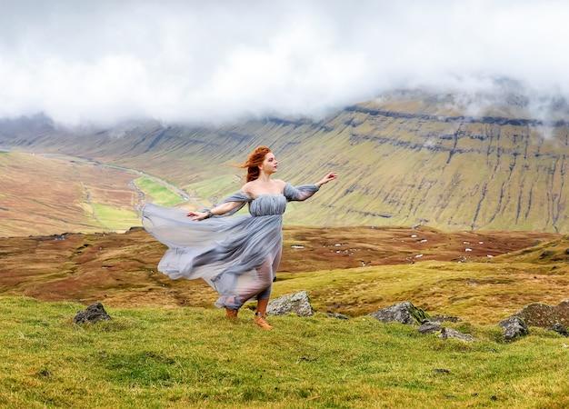 Рыжая девушка-эльфийка в фантазийной одежде танцует в облаках. фарерские острова