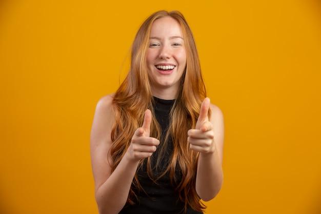 Рыжеволосая девушка на желтой стене предлагает возможность показать пальцем вперед свободное место для рекламного контента.