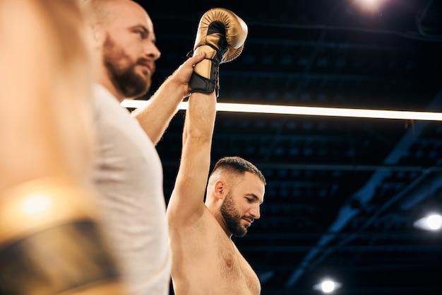 Рефери держит в воздухе руку победителя спарринга
