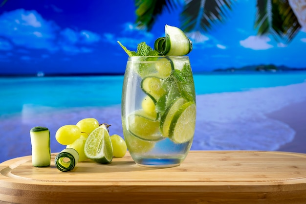 ぼやけた背景のビーチの写真とさわやかなカクテルグラス