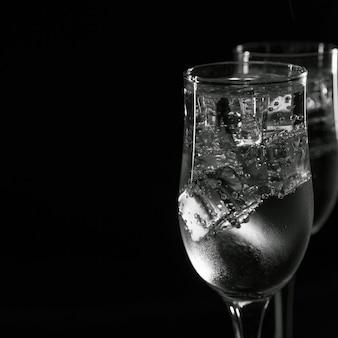 黒の背景に氷とグラスでさわやかな、冷たい飲み物。