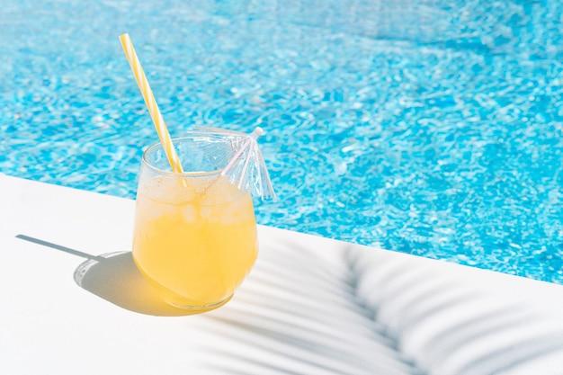 Освежающий фруктовый сок у бассейна в тени пальмы. летний отдых и еда.