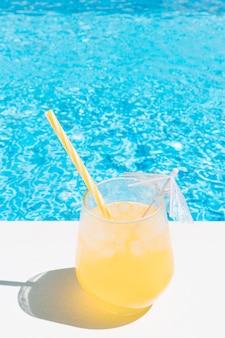 Освежающий фруктовый сок у бассейна. концепция летнего отдыха и еды.