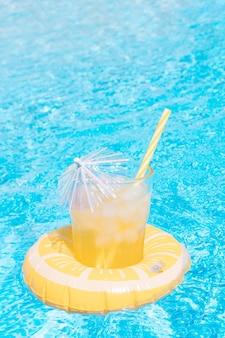 Освежающий фруктовый сок внутри лимона, надувного у бассейна, концепция летнего отдыха и еды.