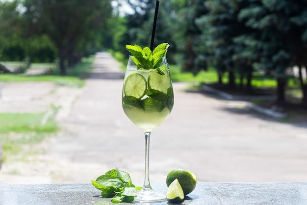ライムのスライスでさわやかな夏のカクテル。アルコール飲料。ミントとアイスキューブの小枝を添えてください。バーで。