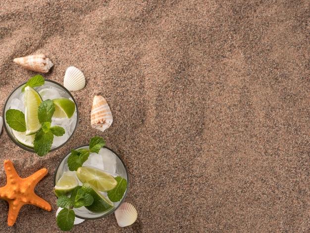 Освежающий летний напиток с лаймом и мятой мохито стоит на песке с ракушками и морскими звездами.