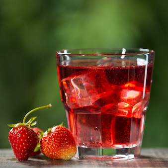 イチゴとアイスキューブのさわやかな夏の飲み物、グラスの横にあるイチゴの果実
