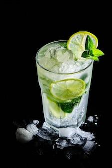 상쾌한 여름 모히또 칵테일. 검은 배경에 얼음과 라임이 있는 알코올 음료.