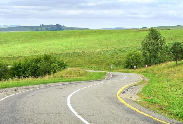 Региональная дорога в сельской местности в степи на фоне зеленых холмов
