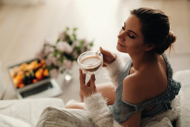 Спокойная девушка дома пьет кофе и смотрит фильм. домашнее спокойствие. девушка удобно сидит на диване и пьет кофе.