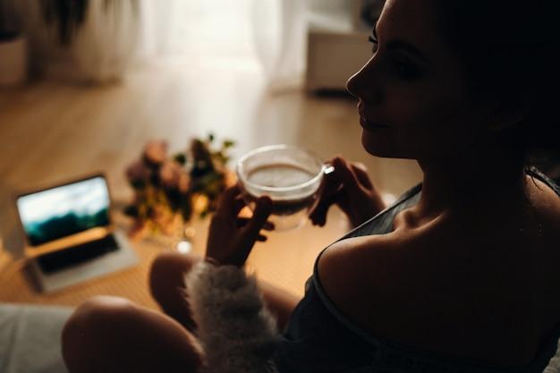 집에서 편안한 여자가 커피를 마시고 영화를보고, 가정에서 차분한 여자가 소파에 편안히 앉아 커피를 마시고있다.