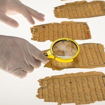 研究者は、虫眼鏡とテーブルを使用してコーランからのアラビア文字を研究します