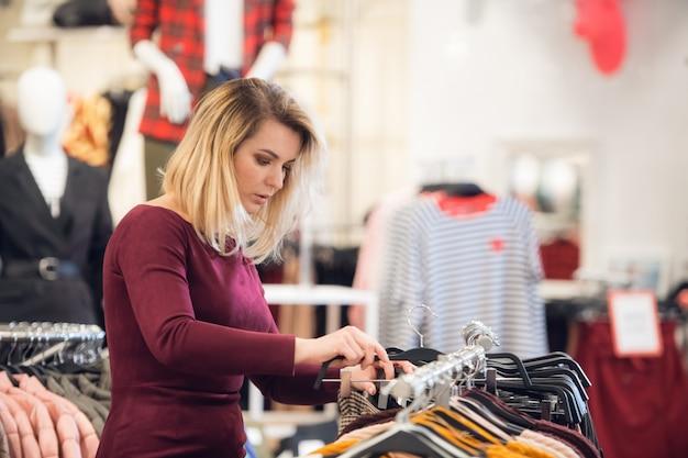 レールの上で服を整理する小売店の従業員