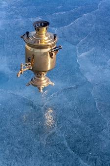 На льду озера стоит ретро-самовар из меди с копией пространства. русский дровяной чайник. красивый голубой лед с трещинами. вертикальный.