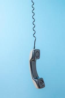 引き伸ばされたワイヤーにぶら下がっているレトロな電話の携帯電話。レトロな通信機器。