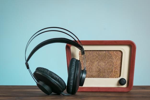 木製のテーブルの横に黒いヘッドフォンが置かれたレトロなラジオ。音声とビデオの再生技術。