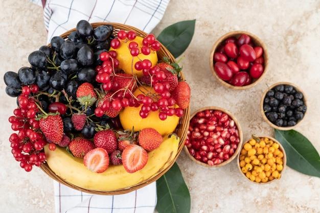 Богатый ассортимент фруктов в мисках и плетеная корзина на полотенце на мраморной поверхности.