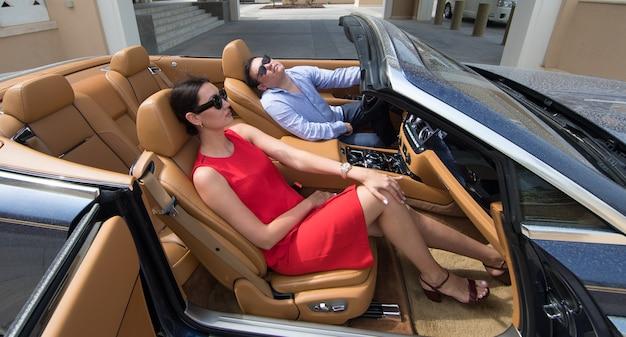 Богатая женщина и мужчина в кабриолете