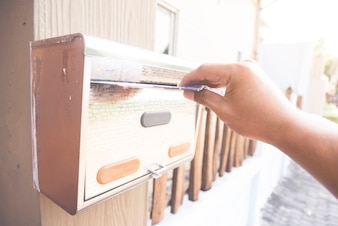 ポストボックスにアジア系スキンの右手が手紙を送る
