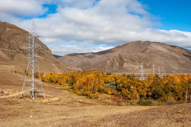 Между горами и желтыми деревьями вдоль берега и линий электропередач протекает река. осенние краски. облака в небе. по горизонтали.