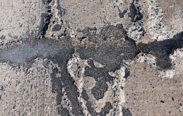質の悪い道路は何度も修理されており、穴や穴の修理が不十分な悪い道路