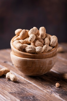 жареный арахис в деревянной миске на темном изображении с выборочным фокусом
