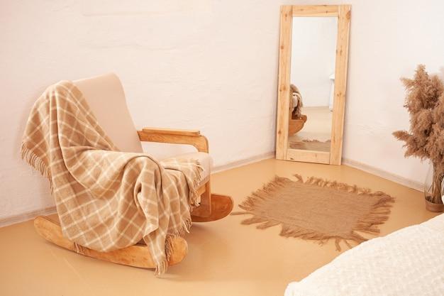Кресло-качалка с пледом, зеркало в деревянной раме.