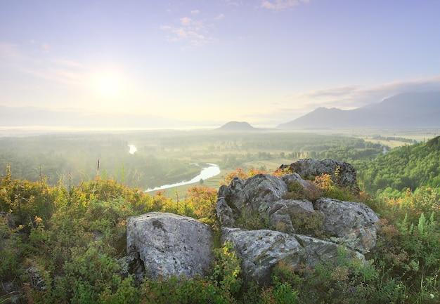 Каменистый склон горы на фоне холмов в тумане в долине реки катуни под золотым небом в горах алтая. сибирь, россия